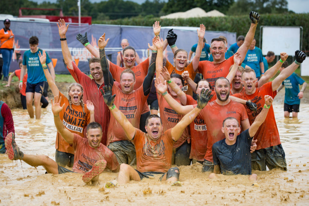 Team in red t-shirts in mud