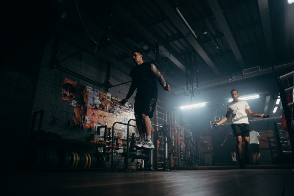 two men jump rope in gym